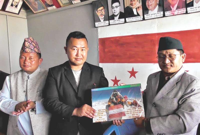 Mt Everest climber Sushil Sherma (centre) handing over a photo with the Nepali Congress flag that was taken atop Everest to NC Panchthar President Narendra Kerung, on Wednesday, May 2, 2018. Photo: THT