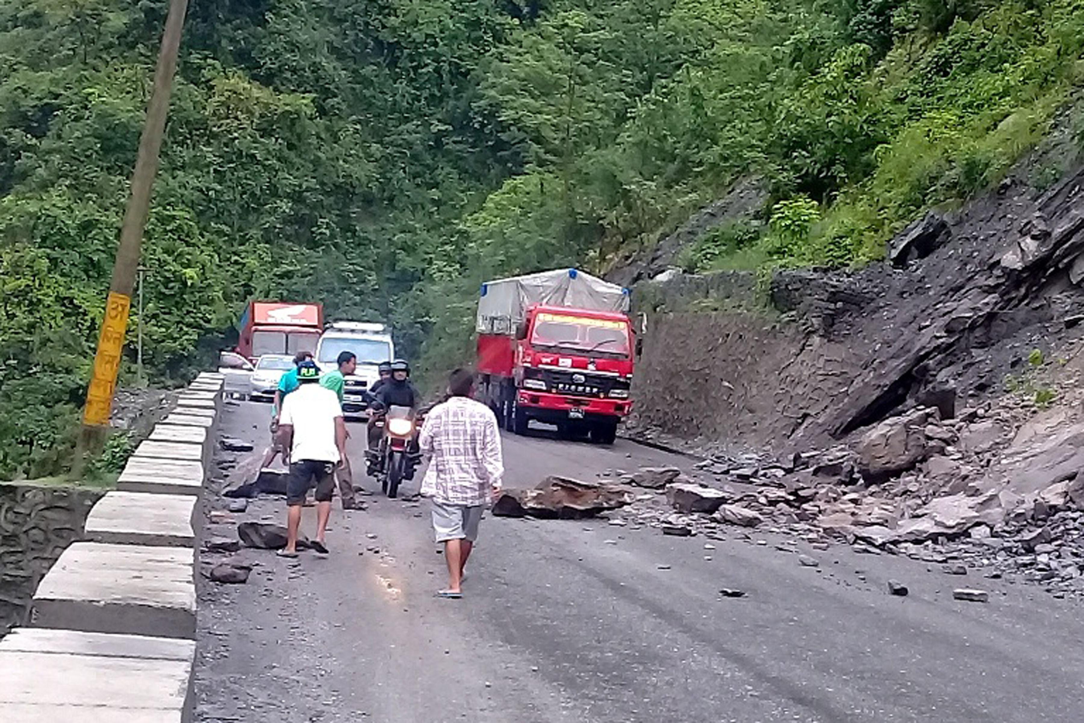 A truck driver and his assistants clear landslide debris off the road while a motorcycle passes by, near Jalbire along the Narayangadh-Muglin road section, in Chitwan district, on Friday, May 18. Photo: RSS