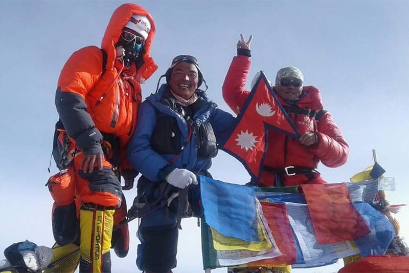 Woman mountaineer Nima Jangmu Sherpa (right) and two other climbers stand atop Mt Everest holding a flag of Nepal, on Monday, May 14, 2018. Photo courtesy: Dawa Sherpa