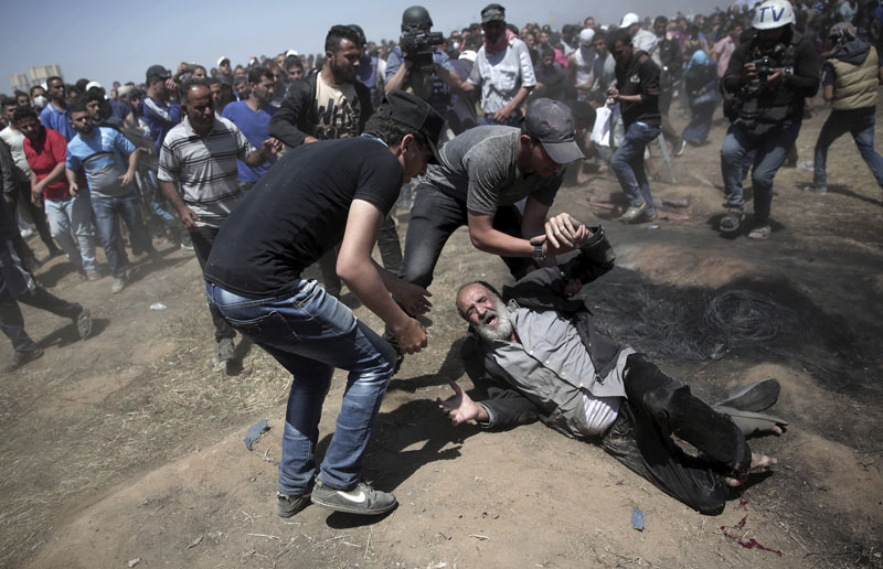 An elderly Palestinian man falls on the ground after being shot by Israeli troops during a deadly protest at the Gaza Strip's border with Israel, east of Khan Younis, Gaza Strip, on Monday, May 14, 2018. Photo: Associated Press