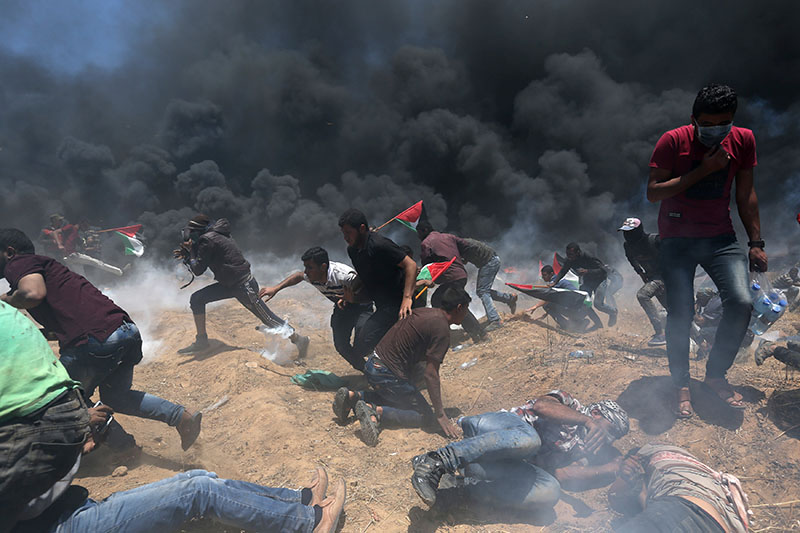 Palestinian demonstrators run for cover from Israeli fire and tear gas during a protest against US embassy move to Jerusalem and ahead of the 70th anniversary of Nakba, at the Israel-Gaza border in the southern Gaza Strip, on May 14, 2018. Photo: REUTERS