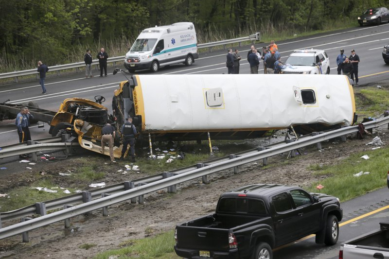 Emergency personnel work at the scene of a school bus and dump truck collision, injuring multiple people, on Interstate 80 in Mount Olive, N.J., on Thursday, May 17, 2018. Photo: APn