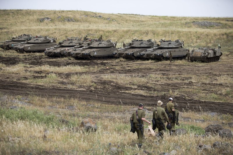 Israeli soldiers walk past tanks in the Israeli-controlled Golan Heights, near the border with Syria, on Thursday, May 10, 2018. Photo: AP