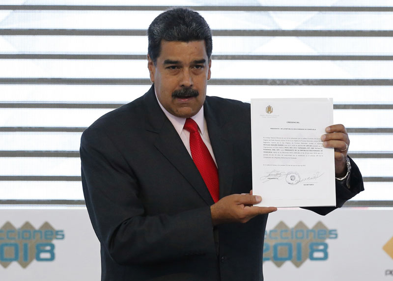 Venezuela's President Nicolas Maduro holds up a National Electoral Council, CNE, certificate declaring him the winner of the presidential election, during a ceremony at CNE headquarters in Caracas, Venezuela, on Tuesday, May 22, 2018. Photo: Associated Press