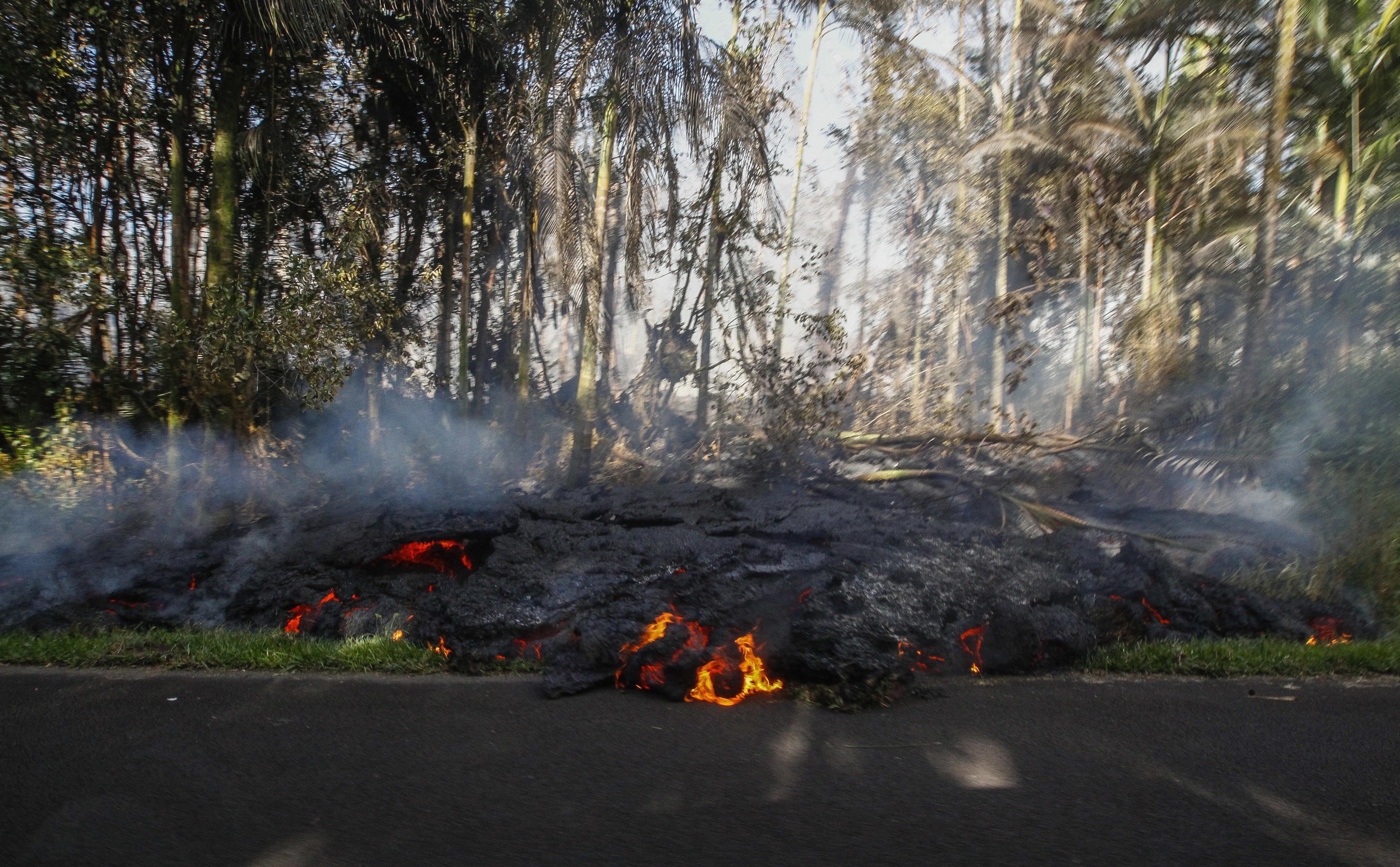 Lava creeps onto the pavement on Luana Street in the Leilani Estates subdivision in Pahoa, Hawaii, on Sunday, May 6, 2018. Photo: Associated Press