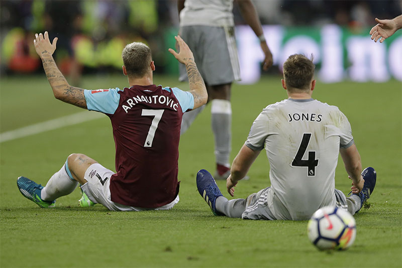 West Ham United's Marko Arnautovic and Manchester United's Phil Jones sit on the pitch during the English Premier League football match between West Ham United and Manchester United at the London Stadium, London, on Thursday, May 10, 2018. Photo: Associated Press