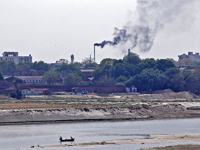 Men row a boat in the river Ganges as smoke emits from a chimney of a leather tannery at an industrial area in Kanpur, India, May 4, 2018. Photo: Reuters