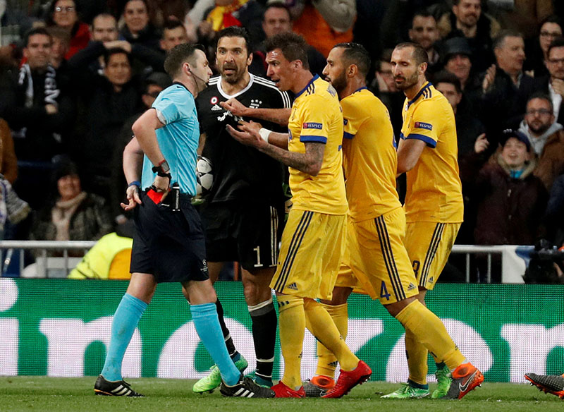 FILE PHOTO: Soccer Football - Champions League Quarter Final Second Leg - Real Madrid vs Juventus - Santiago Bernabeu, Madrid, Spain - April 11, 2018   Juventus' Gianluigi Buffon and team mates remonstrate with referee Michael Oliver after he awarded a penalty to Real Madrid.  REUTERS/Paul Hanna/File Photo