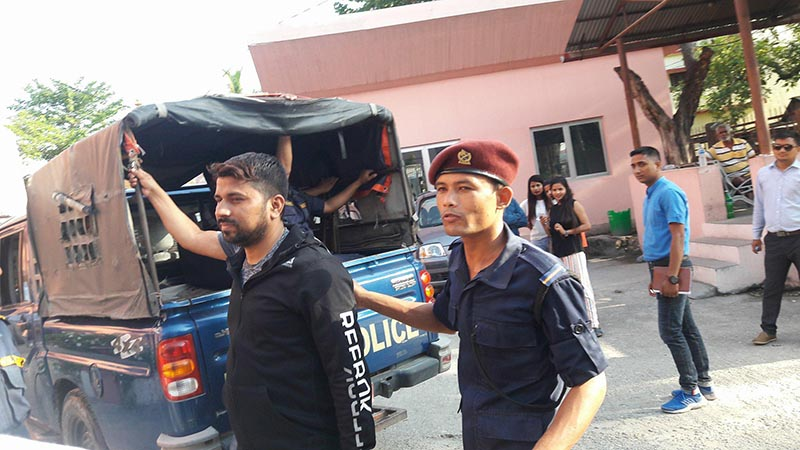 Police escorting a suspect of 33 Kilo gram gold smuggling case to the District Court, Morang, on Tuesday, May 15, 2018. Photo: Keshav Adhikari