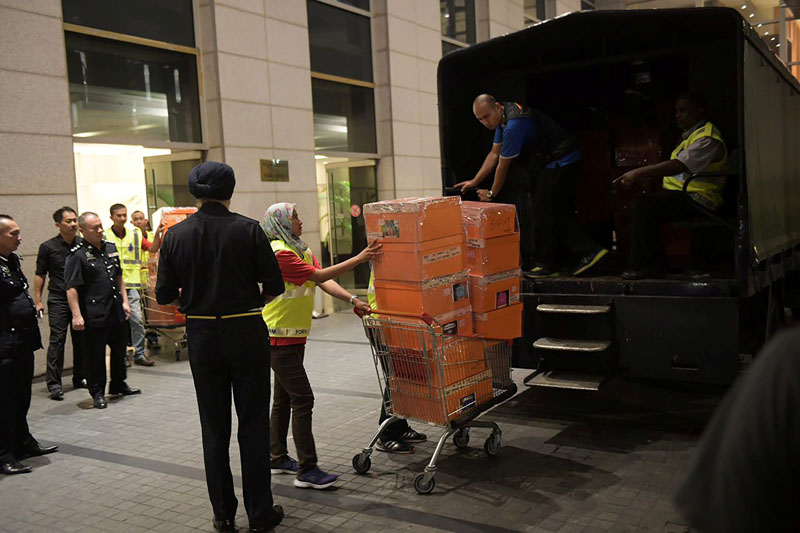 A Malaysian police officer pushes a trolley during a raid of three apartments in a condominum owned by former Malaysian prime minister Najib Razaku2019s family, in Kuala Lumpur, May 17, 2018, in this photo taken by The Straits Times. Picture taken May 17, 2018. Ariffin Jamar/The Straits Times via REUTERS ATTENTION EDITORS -  THIS IMAGE HAS BEEN SUPPLIED BY A THIRD PARTY.  SINGAPORE OUT. NO COMMERCIAL OR EDITORIAL SALES IN SINGAPORE.  FOR EDITORIAL USE ONLY. NO RESALES. NO ARCHIVES.        TPX IMAGES OF THE DAY