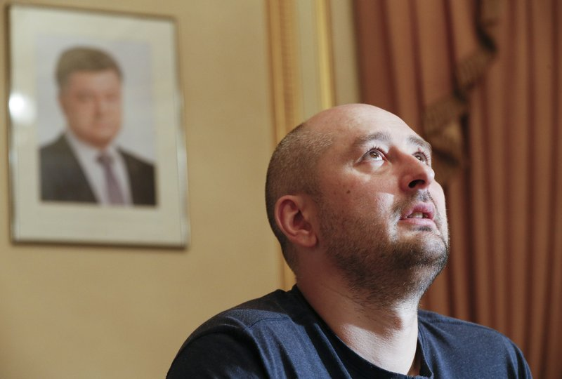 Russian journalist Arkady Babchenko looks up during an interview with foreign media, with the portrait of Ukrainian President Petro Poroshenko, left in the background, in Kiev, Ukraine, on Thursday, May 31, 2018. Photo: AP