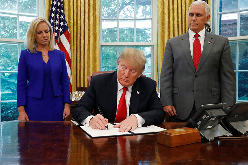 US President Donald Trump signs an executive order on immigration policy with DHS Secretary Kirstjen Nielsen and Vice President Mike Pence at his sides in the Oval Office at the White House in Washington, US, June 20, 2018. Photo: Reuters