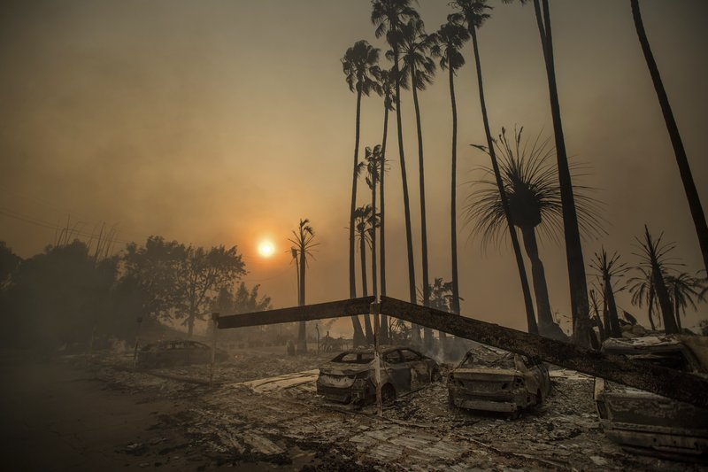 File - In this photo, smoke rises behind a destroyed apartment complex as a wildfire burns in Ventura, California on  Dec. 5, 2017. Photo: AP