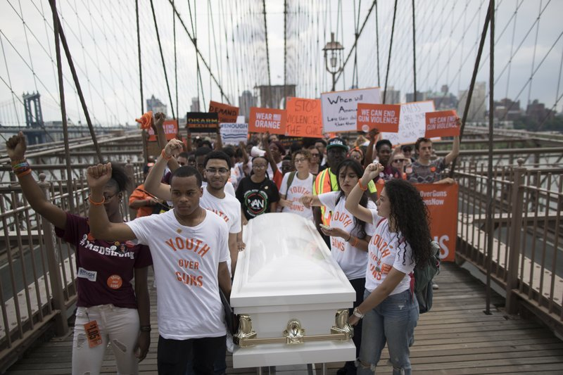 Demonstrators carry a coffin over the Brooklyn Bridge during a march and rally against gun violence, on Saturday, June 2, 2018, in New York.  Photo: APn
