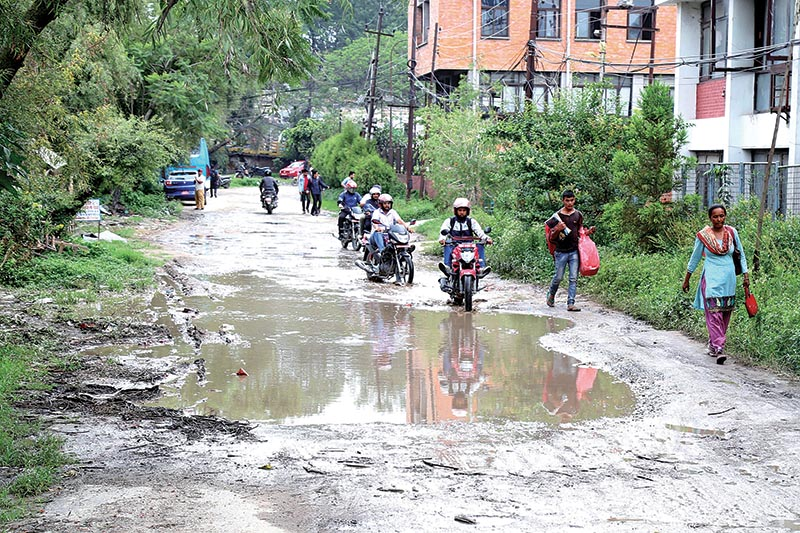 Motorcyclists and pedestrians passing through a road riddled with potholes after a downpour in Kathmandu, on Friday, June 8, 2018. Photo: RSS