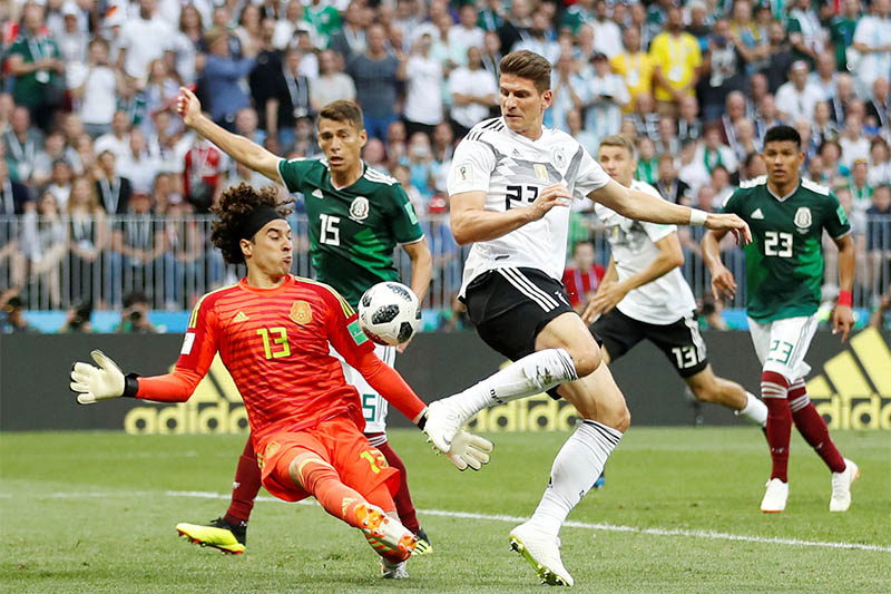 Germany's Mario Gomez shoots at goal as Mexico's Guillermo Ochoa challenges. Photo: Reuters