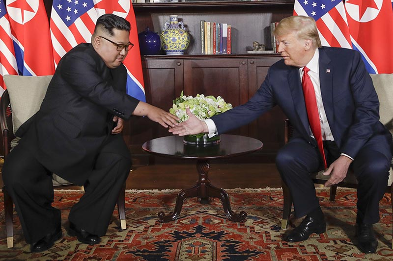 North Korea leader Kim Jong Un reaches to shake US President Donald Trump's hand at the Capella resort on Sentosa Island,  in Singapore, on Tuesday, June 12, 2018. Photo: AP