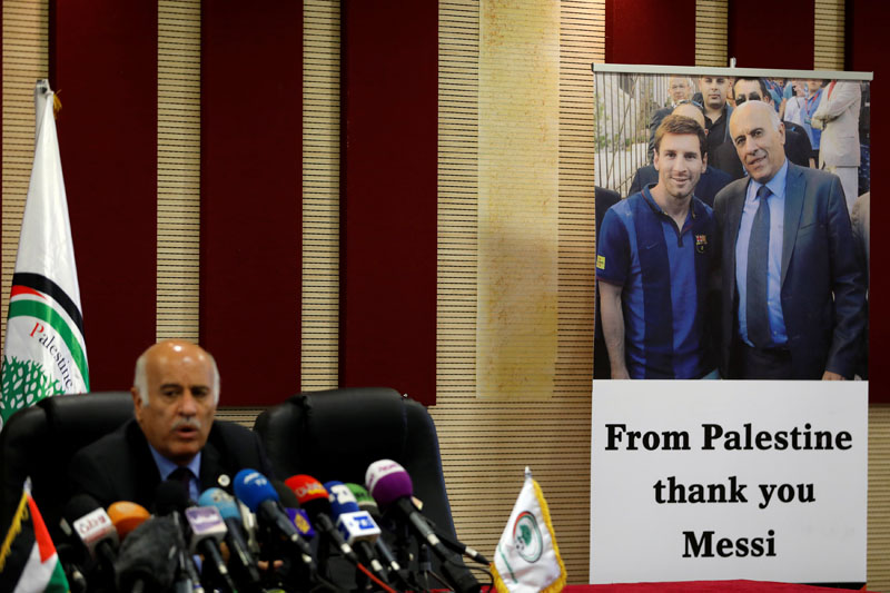 A poster of Palestinian FA chief Jibril Rajoub with Argentina's soccer player Lionel Messi is seen during Rajoub's news conference, in Ramallah in the occupied West Bank June 6, 2018. REUTERS/Mohamad Torokman