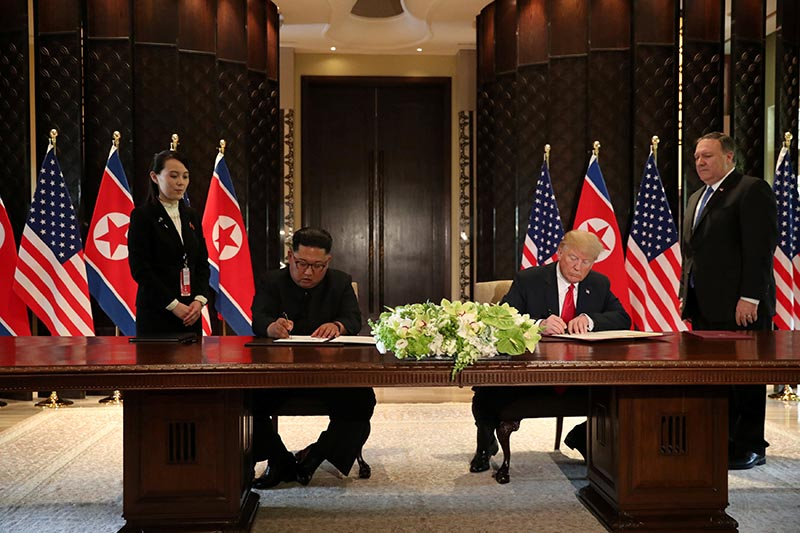 US President Donald Trump and North Korea's leader Kim Jong Un sign documents that acknowledge the progress of the talks and pledge to keep momentum going, after their summit at the Capella Hotel on Sentosa island, in Singapore, on Tuesday, June 12, 2018. Photo: Reuters