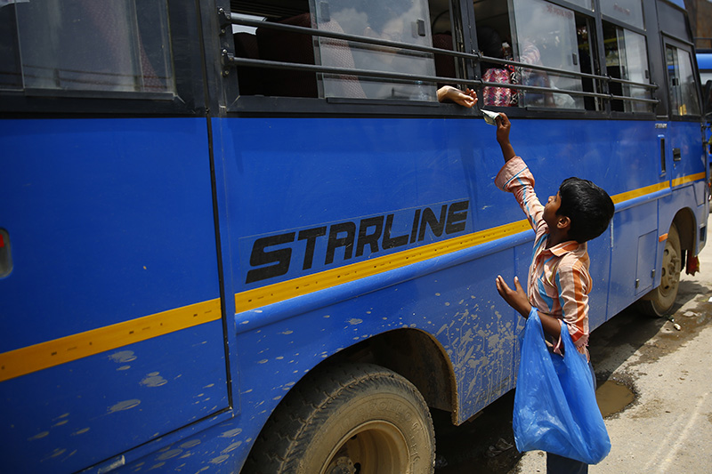 An 8-year-old boy sells mineral water to a passenger at a bus stand on World Day Against Child Labour, in Lalitpur, on Tuesday, June 12, 2018. Photo: Skanda Gautam