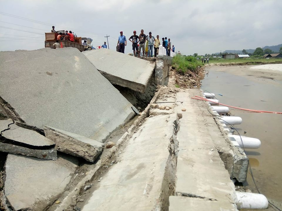 Locals and security personnel inspect a damaged stretch of the Mahuli Bridge along the East-West Highway on Sunday, July 08, 2018. Photo: Byas Shankar Upadhyaya/THT