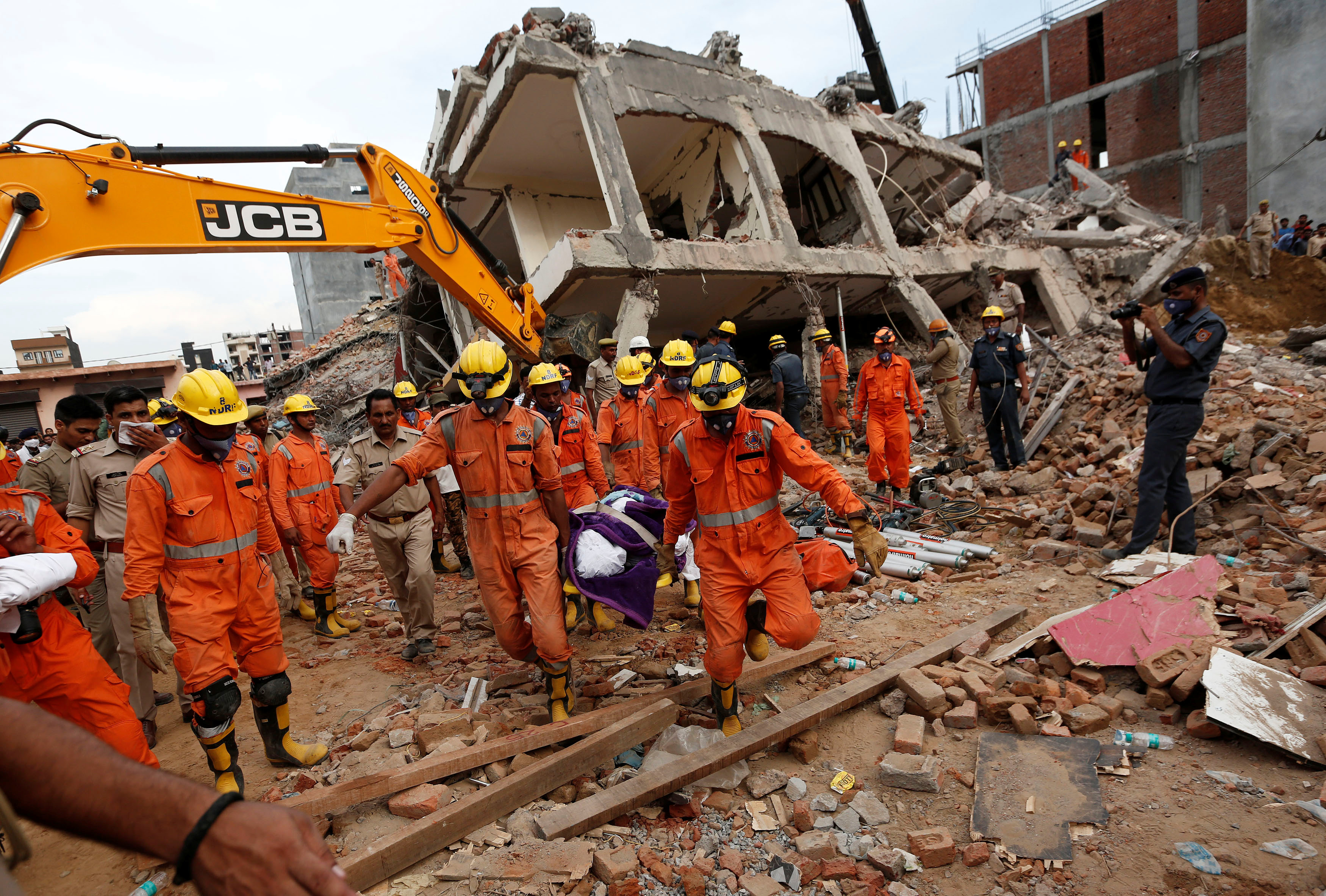 Rescue workers carry the body of a victim at the site of a collapsed residential building at Shah Beri village in Greater Noida, India July 18, 2018. Photo: REUTERS
