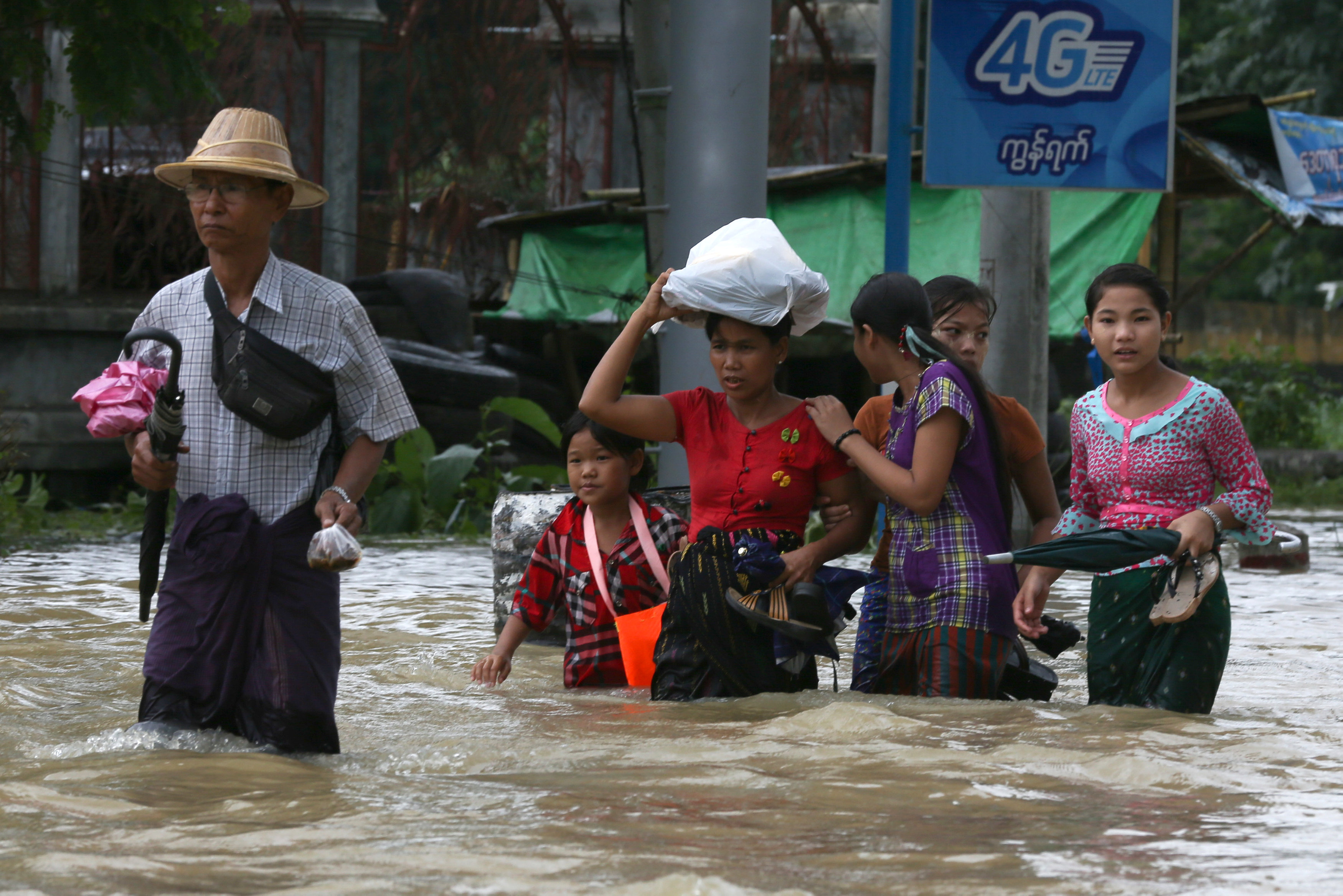 People wade through a flooded street in Bago, Myanmar, July 27, 2018. Picture taken July 27, 2018. Photo: REUTERS