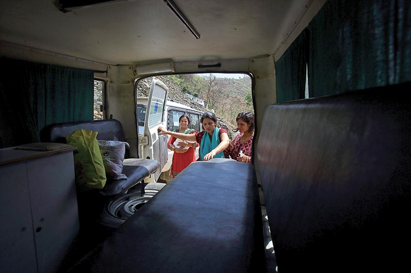 This photo of June 8 shows Pabitra Dhungel (centre) getting into an ambulance a day after giving birth, at a health centre in Ramechhap
