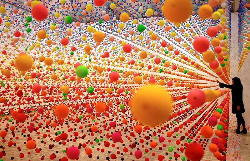 Australian artist Nike Savvas adjusts her installation artwork piece, consisiting of over 50,000 polystyrene balls, titled 'Atomic: full of love full of wonder' as it is installed for the upcoming exhibition 'Spacemakers and roomshakers: installations from the collection' at the New South Wales Art Gallery in Sydney, Australia, July 12, 2018. Picture taken July 12, 2018. Photo: Reuters