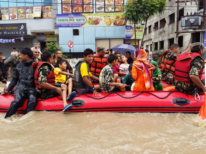 Locals of Bhaktapur area being rescued by security personnel on a rafting boat after the area became inundated following last night's torrential rain, in Bhaktapur, on July 12, 2018. Photo: Anita Shrestha/THT