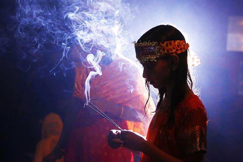 A Hindu girl offers prayer holding incense sticks at a temple during the holy month of Shrawan at Sundarijal, in Kathmandu, on Monday, July 30, 2018. Photo: Skanda Gautam/THT