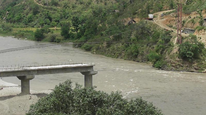 A view of an incomplete bridge over the Tamor River which has been left in limbo after staffers of the construction company fled without completing the project at Lumbuwaghat on the border between Tehrathum and Panchthar. Photo: THT