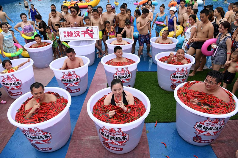 Participants take a bath in barrels filled with chilli peppers during the Spicy Barrel Challenge contest inside a water park in Chongqing, China July 7, 2018. Picture taken July 7, 2018. Photo: Chen Chao/CNS via Reuters