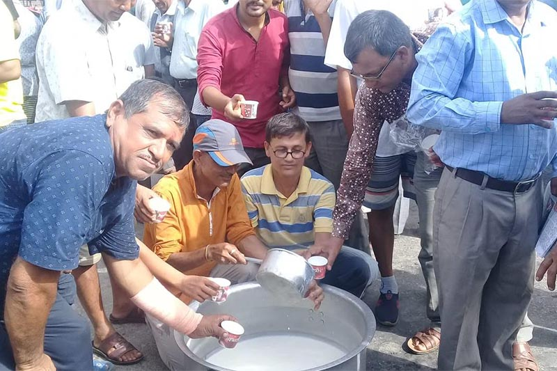 Dairy farmers distributing milk to pedestrians as part of their protest after the price of milk fell in Ratnanagar, Chitwan, on Monday, July 23, 2018. Photo: THT