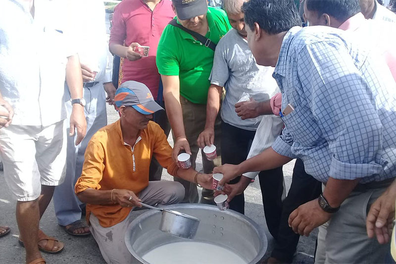 A dairy farmer hands out free milk to pedestrians at Ratnanagar in Chitwan on Monday, July 23, 2018. Photo: Tilak Ram Rimal
