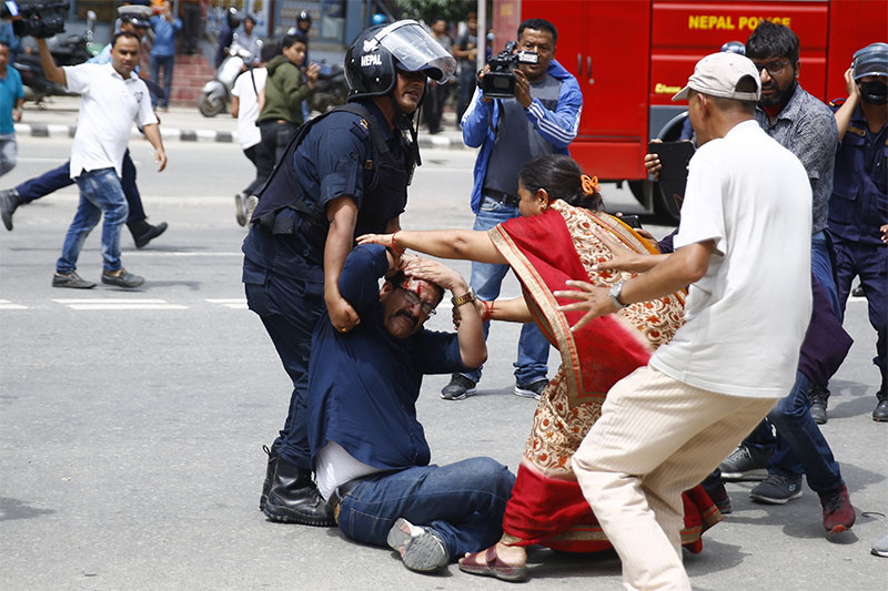 A policeman helps an injured activist of the Tarun Dal during a protest on Saturday, July 21, 2018. Photo: Skanda Gautam