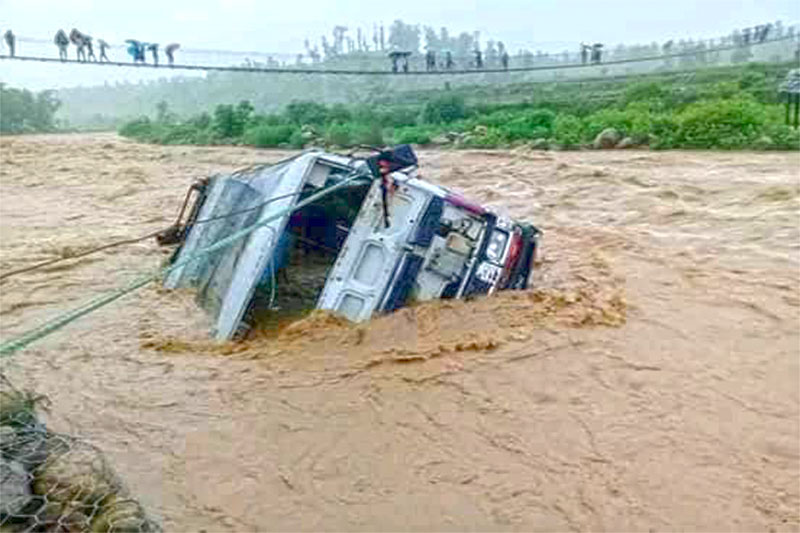 A passenger bus swept  by flood lies roped as locals look from a suspension bridge at Tawang River in Western Dang. No human casualties were reported in the incident. Photo:RSS