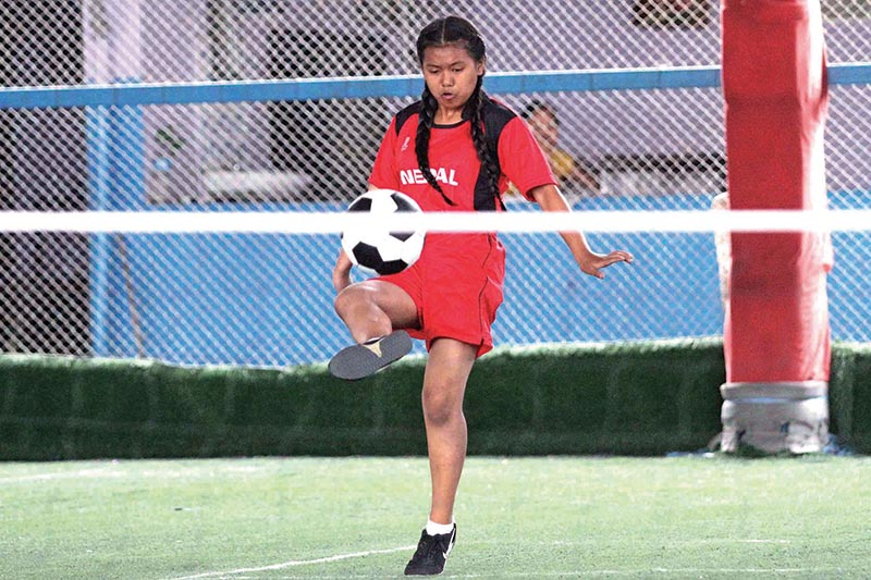 Nepalu2019s Sonia Magar returns to Apsara Begum of India during their Nepal-India Football Tennis Tournament match at the G4 Futsal in Kathmandu on Monday. Photo: THT