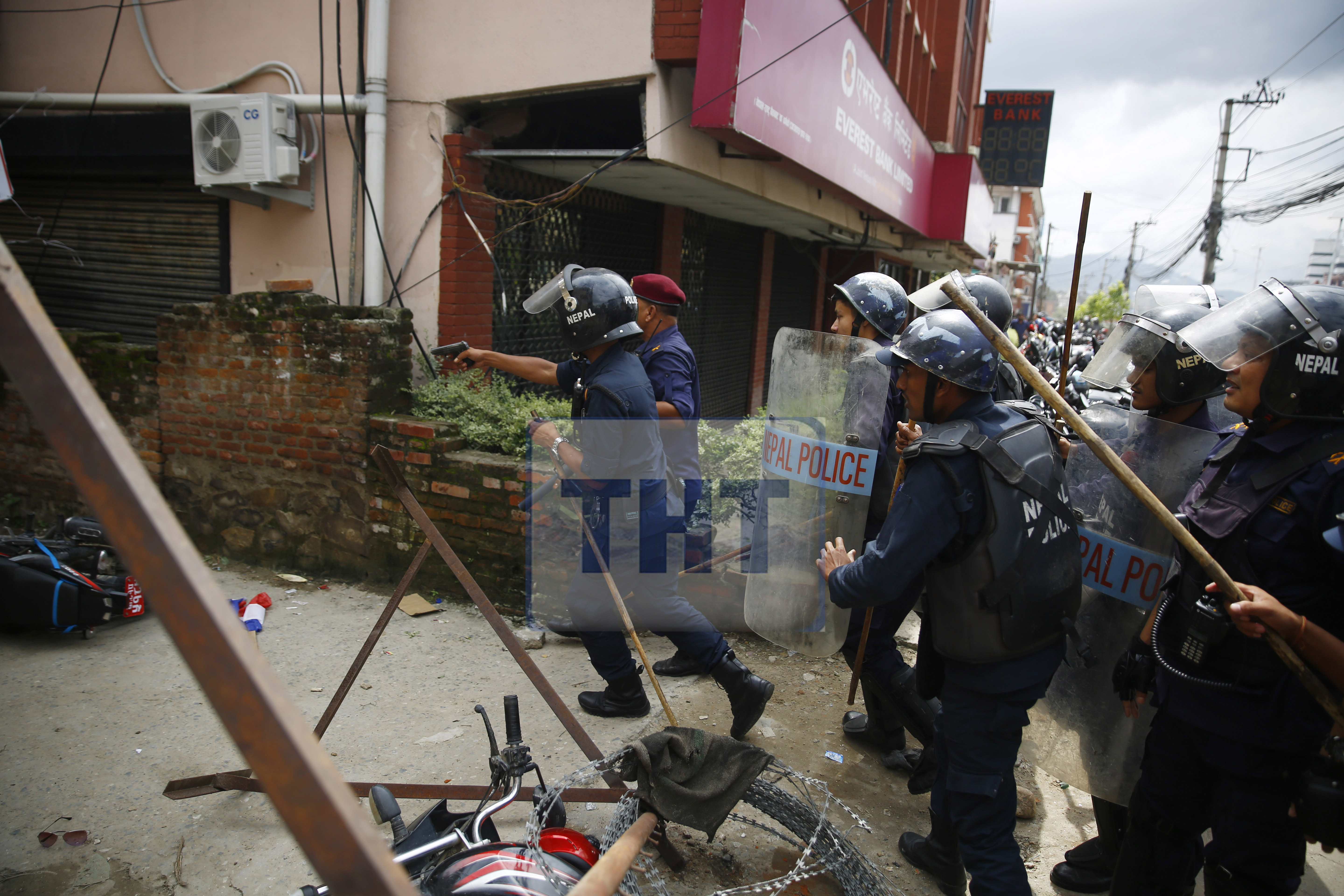 FILE: A policeman threatening demonstrators with a pistol in Baneshwor, Kathmandu, on Saturday. The protesters had gathered in support of Dr Govinda KC. Photo: Skanda Gautam/ THT