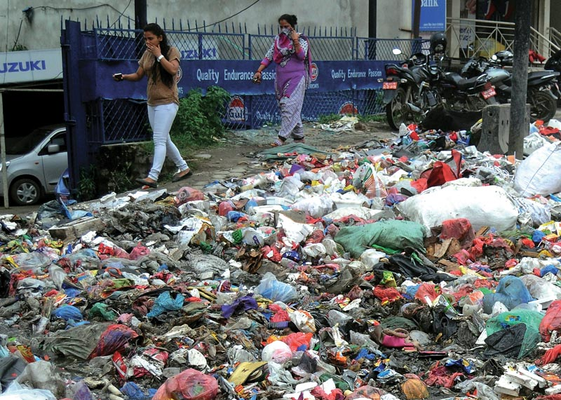 Women covering their noses as they pass through a street littered with garbage, in Kathmandu, on Sunday, July 15, 2018. Photo: THT/file