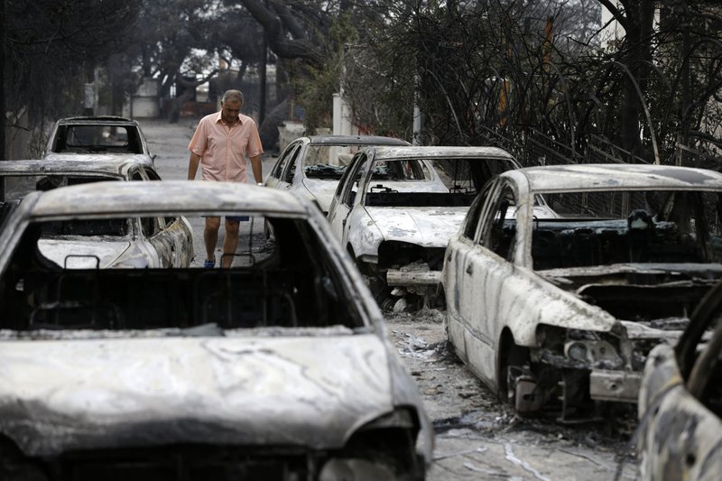 A man passes burned cars in Mati, east of Athens, on Tuesday, July 24, 2018. Photo: AP
