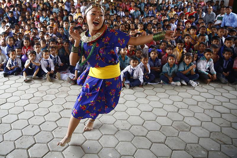 A Nepali school girl dressed in a traditional attire performs during cultural programme held to celebrate 'Guru Purnima' festival or Teacher's Day at a school, in Kathmandu, on Friday, July 27, 2018. Photo: Skanda Gautam/THT