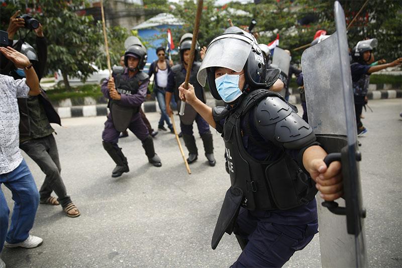A policeman charges batons towards activists of Tarun Dal during a protest at New Baneshwar,  Kathmandu, on Saturday, July 21, 2018. Photo: Skanda Gautam/THT