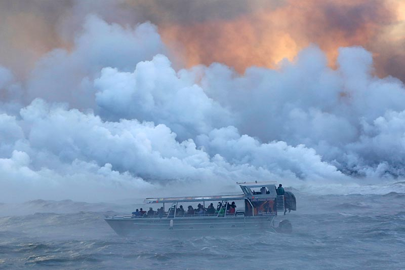 People watch from a tour boat as lava flows into the Pacific Ocean in the Kapoho area, east of Pahoa, during ongoing eruptions of the Kilauea Volcano in Hawaii, US, on June 4, 2018. Photo: Reuters/ File