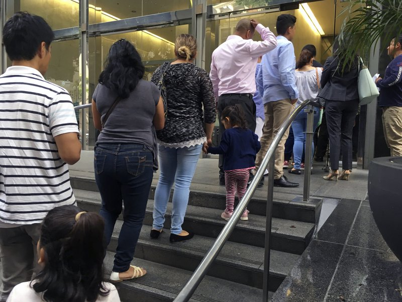 In this photo, people line up outside the building that houses the immigration courts in Los Angeles on June 28, 2018. Photo: AP