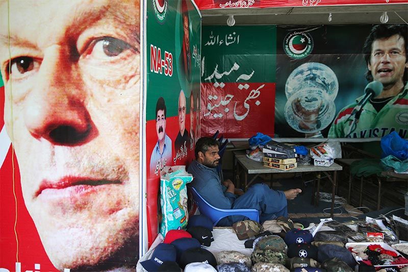A vendor sits next to images of cricket star-turned-politician Imran Khan, chairman of Pakistan Tehreek-e-Insaf (PTI) at a market in Islamabad, Pakistan, July 27, 2018. Photo: Reuters