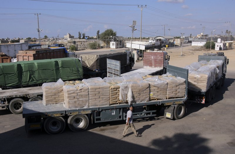 File - In this photo, a Palestinian worker walks next to trucks loaded with sacks of cement at the Kerem Shalom border crossing on its way from Israel to Rafah in the southern Gaza Strip on Tuesday, Oct. 14, 2014. Photo: AP