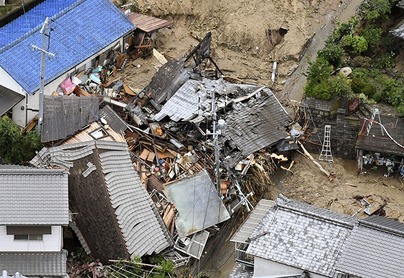 Residential buildings are damaged by a landslide caused by heavy rains in Sakacho, Hiroshima prefecture, south western Japan, on Saturday, July 7, 2018. Photo: Kyodo News via AP
