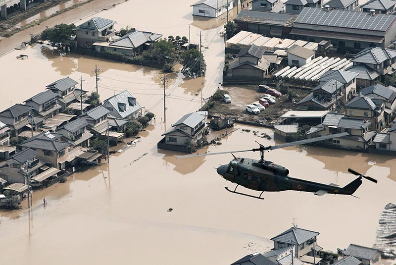 A helicopter flies over Mabi town which was flooded by the heavy rain in Kurashiki, Okayama Prefecture, Japan, on July 9, 2018. Photo:  Kyodo via Reuters