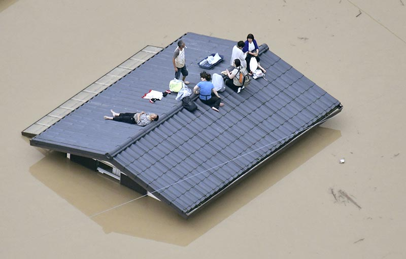 An aerial view shows local residents seen on the roof of submerged house at a flooded area as they wait for a rescue in Kurashiki, southern Japan, on July 7, 2018. Photo: Kyodo/via Reuters